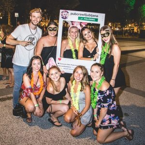 Girls Posing For A Picture With A Pub Crawl Guide In The City Square
