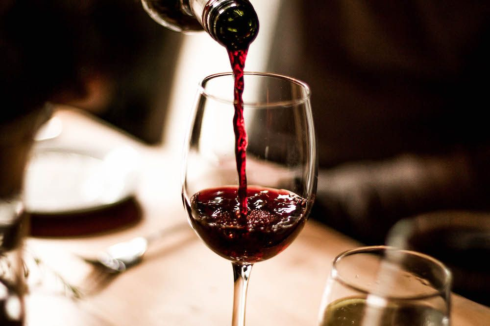 A glass of red wine being poured on a table in a restaurant